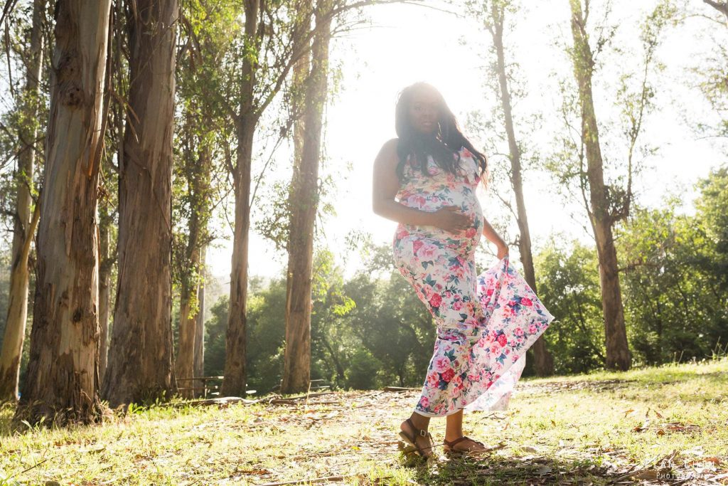 kennedy grove el sobrante maternity shoot with a woman in a floral dress twirling with the sun behind her
