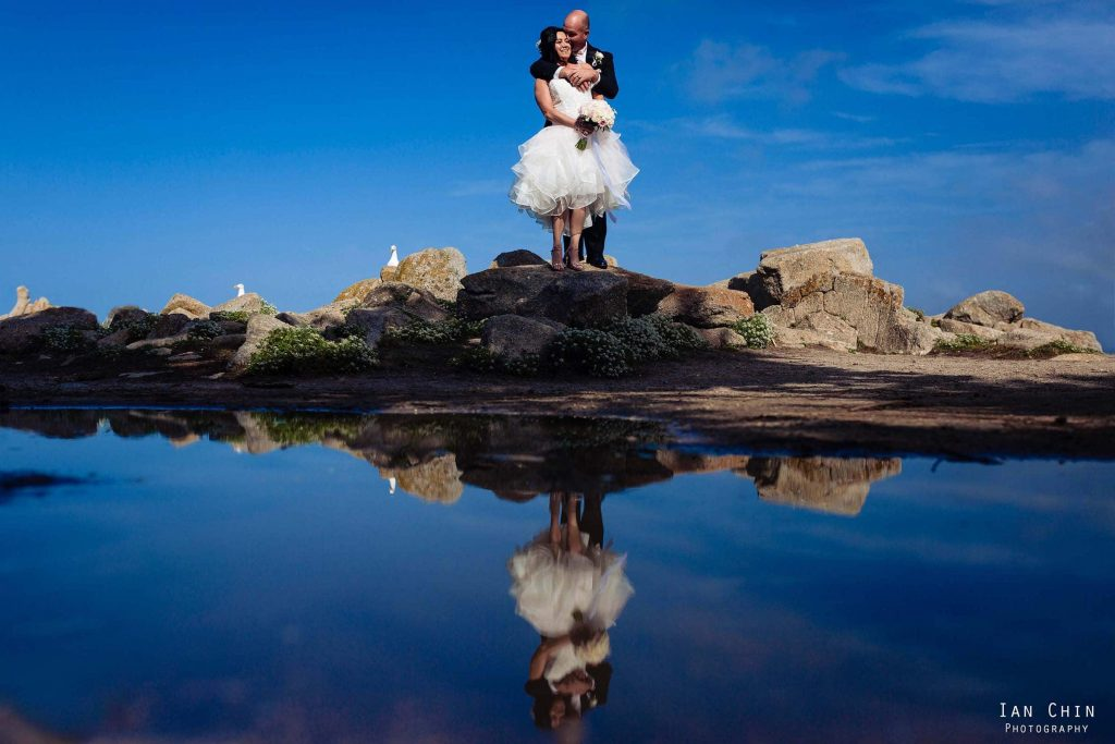 Lovers Point wedding photo with a bride and groom holding each other with their reflection in the water and a blue sky