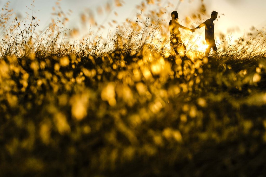 couple running in a field at pearson arastradero perserve in palo alto during sunset