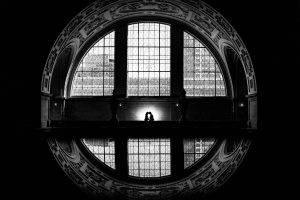 san francisco city hall wedding photographer black and white photo of a couple silhouetted within a circle window reflection