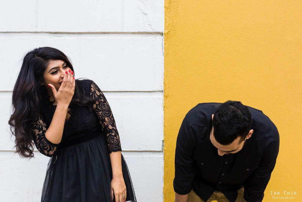 san francisco engagement shoot at alamo square with a white and yellow wall and the couple laughing
