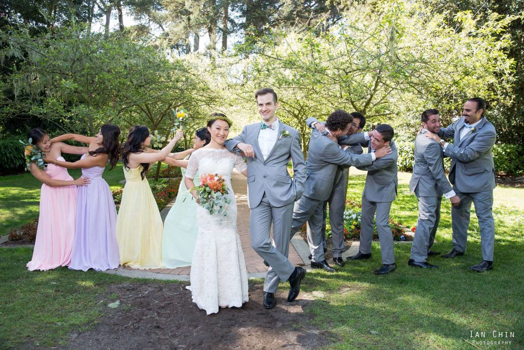 shakespeare garden wedding with bride and groom smiling in the middle while the wedding party is pretend fighting