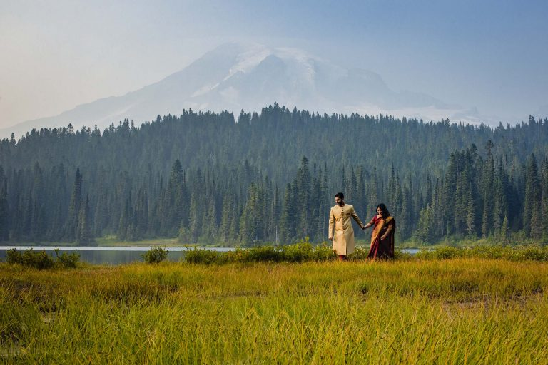 Mt Rainier Elopement with indian couple in traditional wardrobe walking with mount rainier in the background