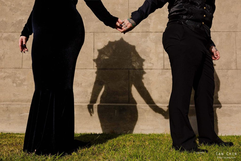 cemetery wedding with the two brides holding hands and the shadow of her wedding gown showing on the wall