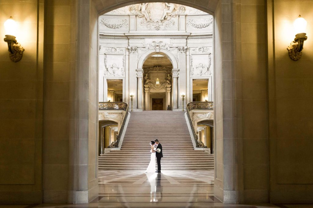 bride and groom dancing in front of the grand staircase in San Francisco City Hall wedding photographer