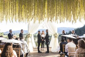 auberge du soleil wedding flowers hanging as two grooms hold hands in front of their wedding guests