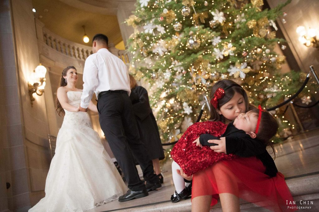 san francisco city hall big sister in a red dress kissing her baby sister while her parents are getting married behind them standing in front of a christmas tree