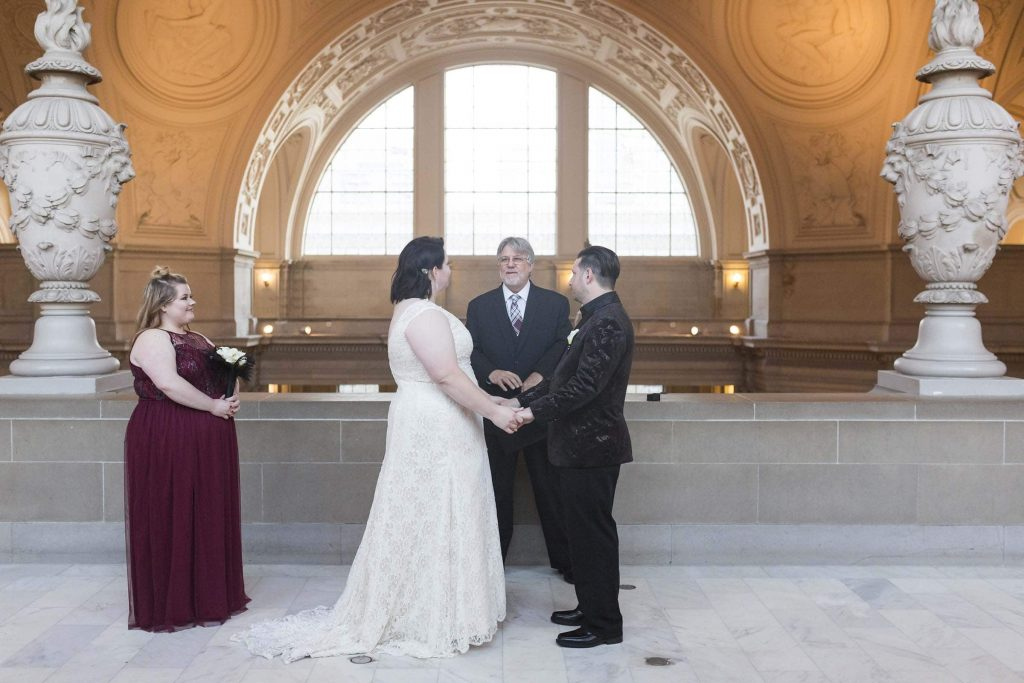 san francisco city hall fourth floor wedding bride and groom holding hands with one maid of honor in a burgundy dress