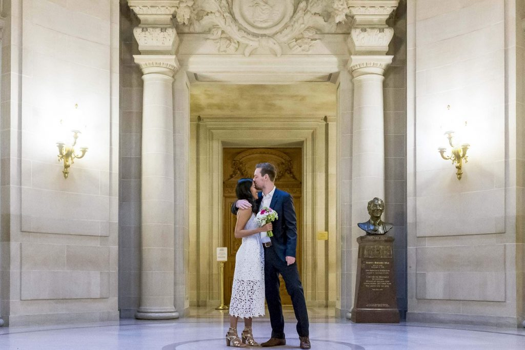 san francisco city hall rotunda wedding with bride getting a kiss from groom wearing a suit