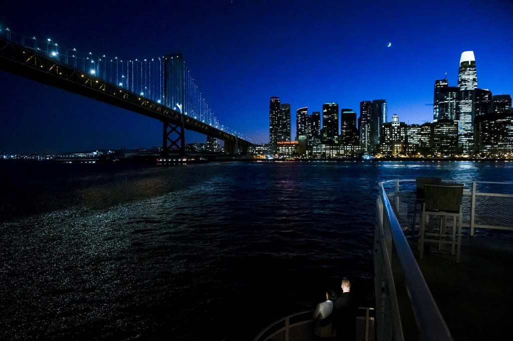 hornblower cruise wedding evening photo with san francisco skyline in the background and bay bridge